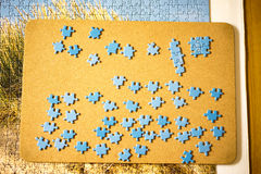 Jigsaw puzzle pieces laid on on a board Stock Photo