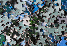 Jigsaw Puzzle Pieces. Loose pieces of jigsaw puzzle, some turned over showing the backside, mainly in blues and greens Royalty Free Stock Photography
