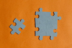 Jigsaw puzzle pieces on orange background Royalty Free Stock Photography