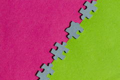 Jigsaw Puzzle pieces on pink and green background. Jigsaw Puzzle pieces on border between pink and green background with copy space Royalty Free Stock Photo