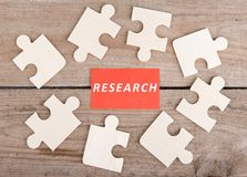 Jigsaw Puzzle Pieces with text & x22;Research& x22; on wooden background. Business Teamwork Concept - Jigsaw Puzzle Pieces with text & x22;Research& x22; on stock image