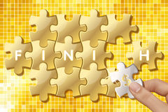 Jigsaw puzzle pieces with words finish. Hands holding jigsaw puzzle pieces with Dollar sign and words finish on gold background Royalty Free Stock Image