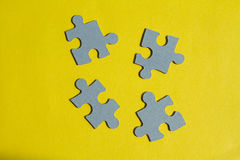 Jigsaw Puzzle pieces on yellow background Stock Image