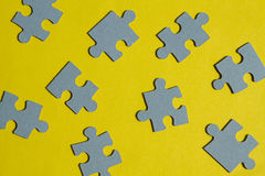 Jigsaw Puzzle pieces on yellow background Stock Photo