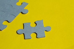 Jigsaw Puzzle pieces on yellow background Royalty Free Stock Photography