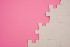 Jigsaw puzzle on a pink background Royalty Free Stock Images