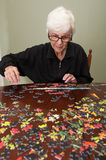 Jigsaw puzzle put together by an eldery woman Royalty Free Stock Photography
