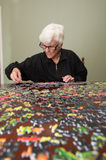 Jigsaw puzzle put together by an eldery woman Stock Photos