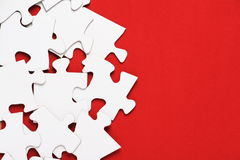 Jigsaw Puzzle on Red. Blank Jigsaw Puzzle pieces on a bright red background Royalty Free Stock Images