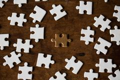 Jigsaw puzzle scattered brown on the floor of wooden planks, B stock images