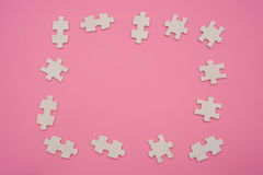 Jigsaw puzzle shaped as a frame on pink Stock Photos