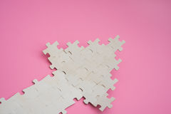 Jigsaw puzzle shaped like an arrow going up on pink Stock Photos