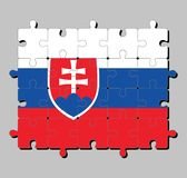 Jigsaw puzzle of Slovakia flag in white blue and red; charged with a shield containing a white cross is placed to left of center. Concept of Fulfillment or stock illustration