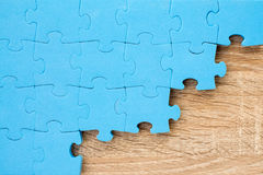 Jigsaw puzzle on wooden background Royalty Free Stock Image