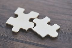 Jigsaw puzzle on wooden background top view - Two jigsaw piece connecting stock photos