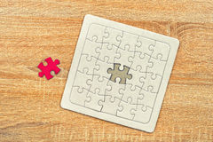 Jigsaw puzzle on wooden table Royalty Free Stock Photography