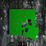 Jigsaw puzzles made out of green grass, on grunge dark concrete floor background royalty free stock images