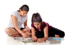 Jigsaw Puzzling. A young teen and preteen sisters working on a complicated jigsaw puzzle Stock Image