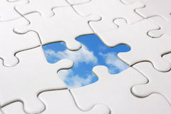Jigsaw sky. Jigsaw puzzle with missing piece revealing blue sky Royalty Free Stock Images