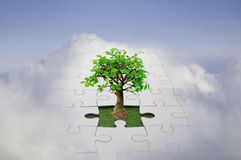 Jigsaw sky. Small tree growing from a jigsaw in the sky symbolising the growth of new ideas and discovering solutions Royalty Free Stock Photos