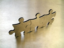 Jigsaw team. Three metallic jigsaw pices on a steel background stock photography