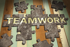 Jigsaw teamwork. Teamwork concept with  jigsaw puzzle on wooden table background,business concept Stock Images