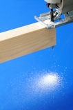 Jigsaw to saw a piece of wood. Jigsaw sawing a piece of wood, focus on saw Stock Photo