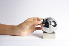 Jigsaw World. A hand assembling the last piece of a jigsaw puzzle that is in the shape of the world Stock Photos