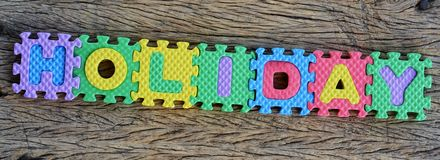 Jigsaw written holiday word on wood background Stock Photography