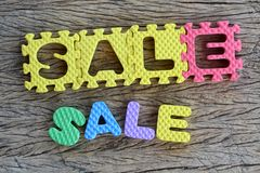 Jigsaw written sale word on wood background Royalty Free Stock Photography