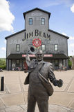Jim Beam Distillery. CLERMONT, Kentucky, USA - June 18, 2016: Tourists visit the Jim Beam Stillhouse, shown with a statue of James Beam in front of it, on June Royalty Free Stock Images