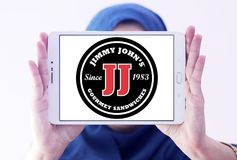 Jimmy John`s sandwich restaurant logo. Logo of Jimmy John`s restaurant on samsung tablet holded by arab muslim woman. Jimmy John`s Franchise, LLC is a franchised royalty free stock photography