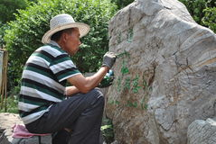 Jinan, China, 7 Juni 2015 Chinese mens die Chinees karakter op een steen schilderen Stock Fotografie