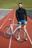 Jinete alegre barbudo de la bicicleta en pista; Foto de archivo libre de regalías