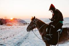 Jinete asiático nacional con el caballo en una puesta del sol Fotografía de archivo