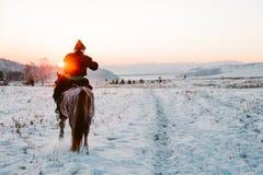 Jinete asiático nacional con el caballo en una puesta del sol Fotos de archivo libres de regalías