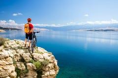 Jinete biking de la montaña que mira el mar y las montañas inspiradores Foto de archivo