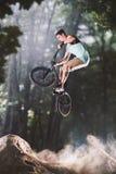 Jinete de la bici de Bmx en el bosque Imágenes de archivo libres de regalías