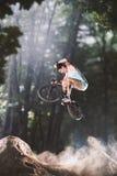 Jinete de la bici de Bmx en el bosque Foto de archivo