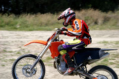 Jinete de la bici de Moto que apresura X con el fondo enmascarado como él acomete más allá en pista de suciedad Imagenes de archivo