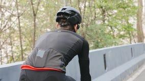 Jinete de la bici que lleva el equipo negro y rojo en la bicicleta en el parque Detr?s cerca para arriba siga el tiro Concepto de almacen de metraje de vídeo