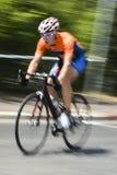 Jinete de la bicicleta con la camisa anaranjada en el movimiento foto de archivo libre de regalías