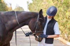 Jinete de la chica joven, con un caballo colocándose en el aire fresco Foto de archivo