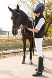Jinete de la chica joven, con un caballo colocándose en el aire fresco Fotografía de archivo libre de regalías