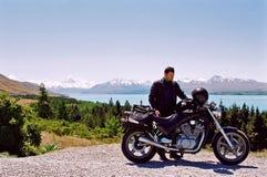 Jinete de la motocicleta cerca de la montaña y del lago imágenes de archivo libres de regalías
