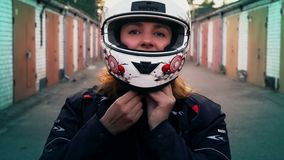 Jinete de la mujer del pelirrojo que pone en casco de la motocicleta Retrato de la muchacha del motorista, forma de vida de la ge almacen de video