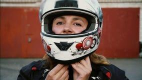 Jinete de la mujer del pelirrojo que pone en casco de la motocicleta Retrato de la muchacha del motorista, forma de vida de la ge almacen de metraje de vídeo