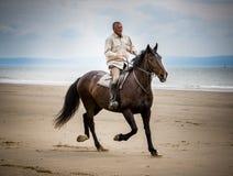 Jinete del caballo de la playa Imagenes de archivo