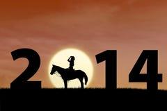 Jinete del caballo en la puesta del sol con 2014 Foto de archivo