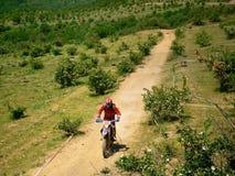 Jinete del motocrós en un camino de tierra Fotos de archivo
